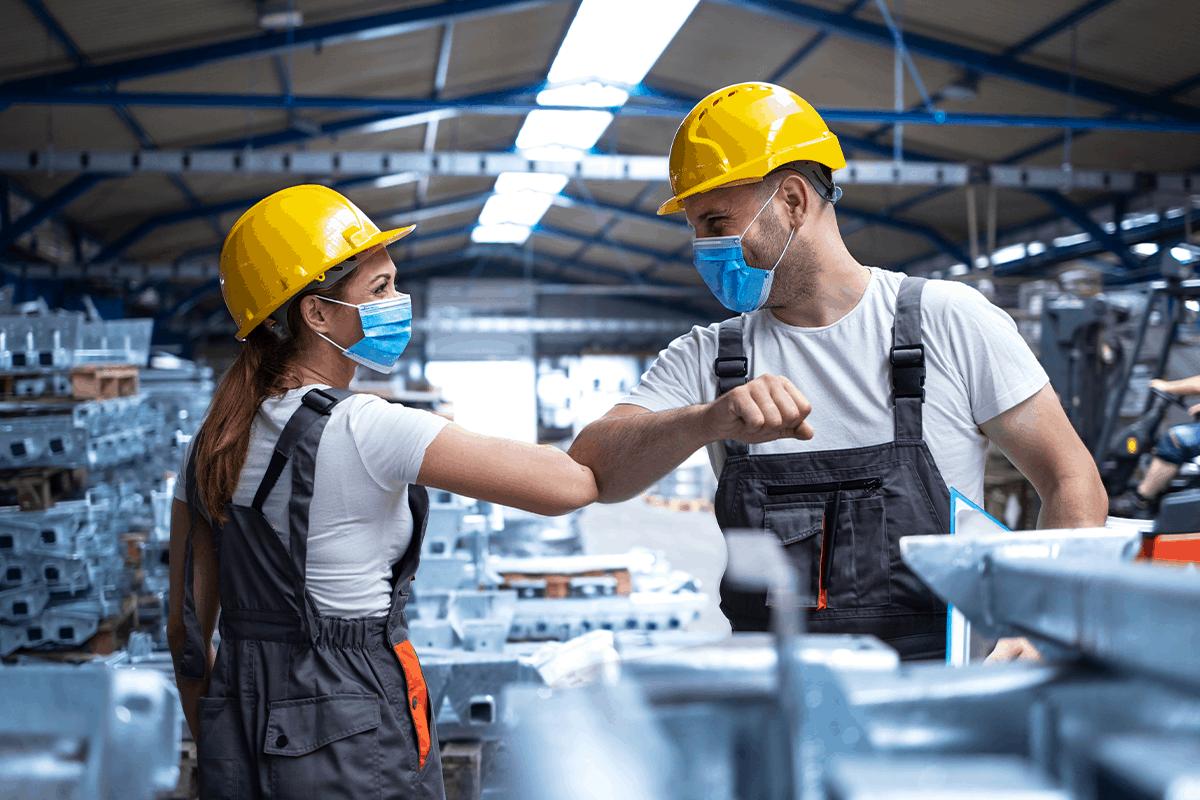 Factory workers practice safe COVID-19 procedures